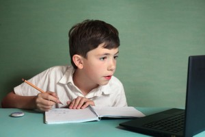 preteen handsome boy has online drawing lesson
